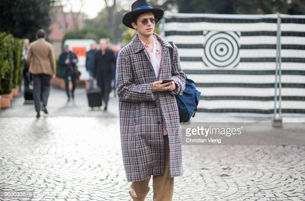 Alessandro Enriquez wearing hat checked coat beige track suit is seen during the 93 Pitti Immagine Uomo at Fortezza Da Basso on January 9 2018 in...
