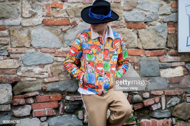 Alessandro Enriquez wearing hat colorful jacket beige track suit is seen during the 93 Pitti Immagine Uomo at Fortezza Da Basso on January 9 2018 in...