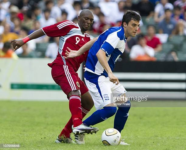 Alessandro Ferreira Leonardo of Hong Kong League XI and Miguel Madera of Birmingham City compete for the ball during the Xtep Cup as part of...