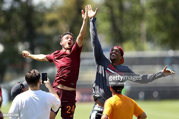Alessandro Florenzi of AS Roma jumps for a basketball with NBA player Evan Turner of the Portland Trail Blazers during a friendly match against the...