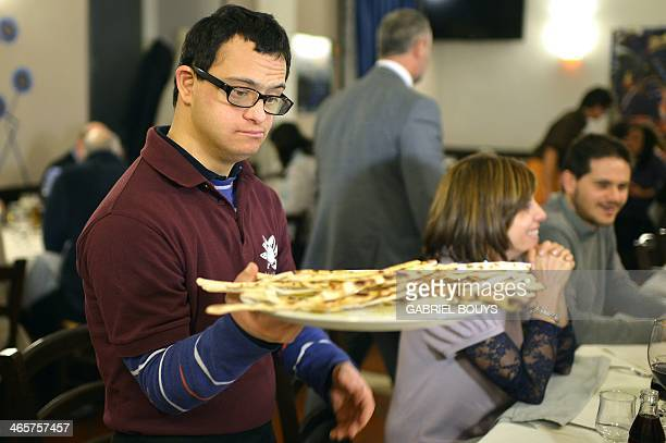 Alessandro Giusto a young men with Down syndrome works at the restaurant 'Locanda dei Sunflowers' on January 28 2014 in Rome This restaurant is born...
