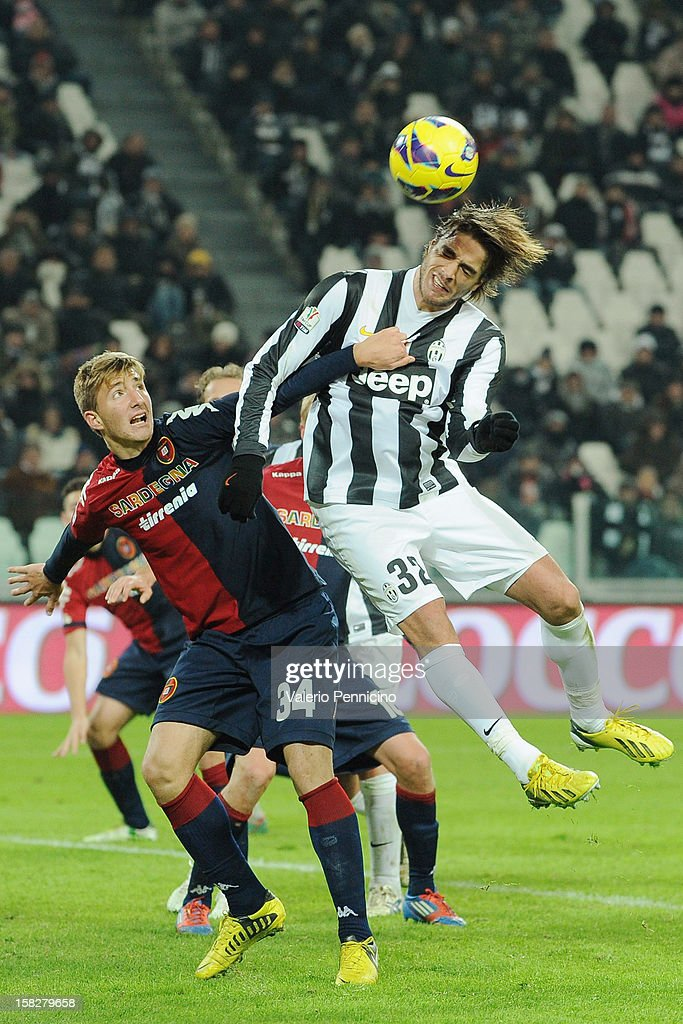 Alessandro Matri (R) of Juventus FC is pulled by his shirt by Dario Del Fabro of Cagliari Calcio during the TIM Cup match between Juventus FC and Cagliari Calcio at Juventus Arena on December 12, 2012 in Turin, Italy.