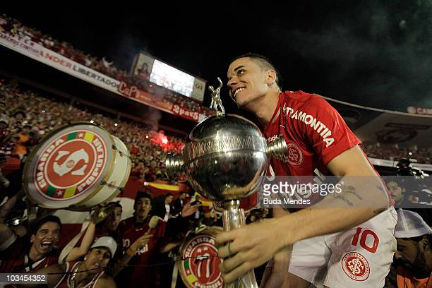 Alessandro of Internacional lift the trophy with fans after winning the match against Mexico's Chivas Guadalajara as part of Final 2010 Copa...
