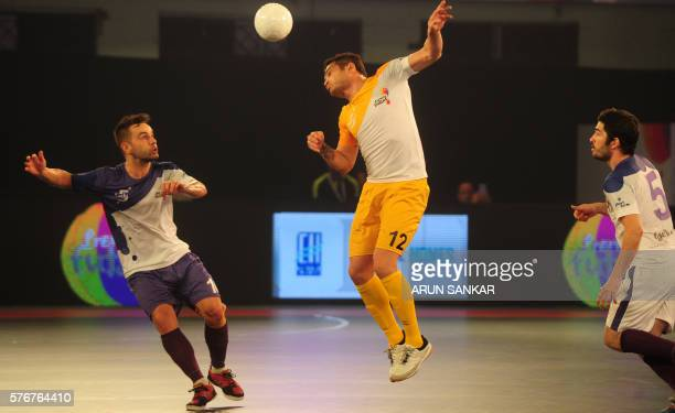 Alessandro Rosa Viera also known as Falcao from the Chennai 5's heads the ball as he plays against the Kochi 5's Devies Moraes and Gekabert during...