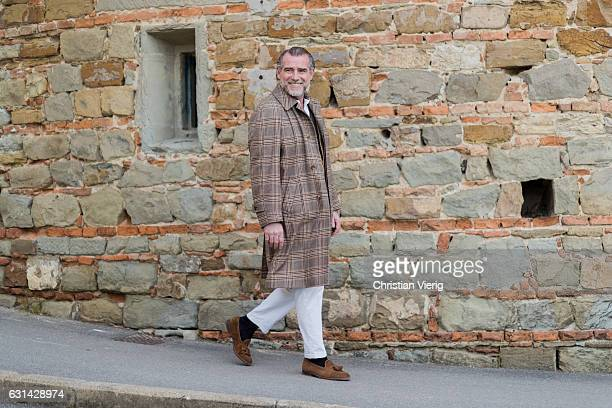 Alessandro Squarzi is wearing a brown checked coat white pant on January 10 2017 in Florence Italy