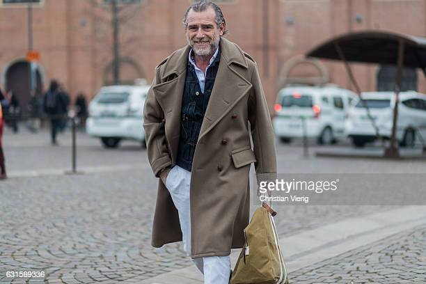 Alessandro Squarzi is wearing a brown wool coat denim jacket white pants on January 12 2017 in Florence Italy