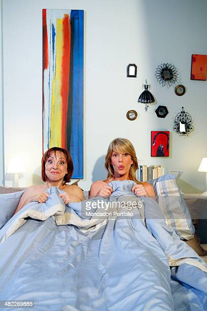 Alessia Marcuzzi and Debora Villa both halfdressed pose under the blanket during a photo shoot on the set of Vous les femmes in 2008 at Villa...