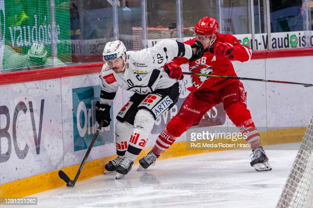 Alessio Bertaggia of HC Lugano battles for the puck with Lukas Frick of Lausanne HC during the Swiss National League match between Lausanne HC and HC...