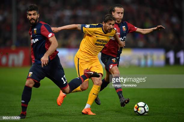 Alessio Cerci of Hellas Verona FC in action against Luca Rossettini and Diego Laxalt of Genoa CFC during the Serie A match between Genoa CFC and...