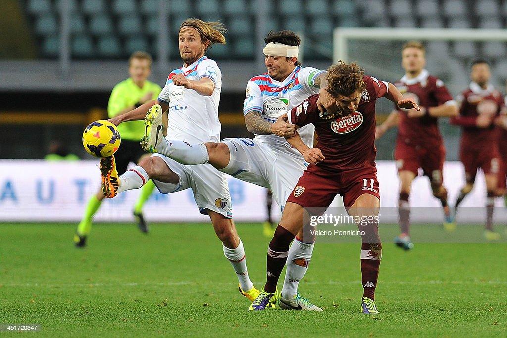 Alessio Cerci (R) of Torino FC clashes with Pablo Alvarez (C) of Calcio Catania during the Serie A match between Torino FC and Calcio Catania at Stadio Olimpico di Torino on November 24, 2013 in Turin, Italy.