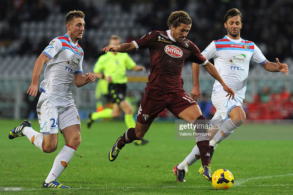 Alessio Cerci (C) of Torino FC in action against Norbert Gyomber (L) and Nicola Legrottaglie of Calcio Catania during the Serie A match between Torino FC and Calcio Catania at Stadio Olimpico di Torino on November 24, 2013 in Turin, Italy.