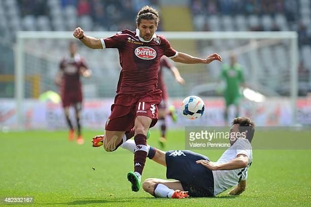 Alessio Cerci of Torino FC is challenged by Davide Astori of Cagliari Calcio during the Serie A match between Torino FC and Cagliari Calcio at Stadio...