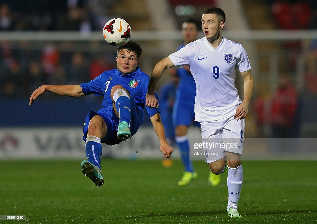 Alessio Lo Porto of Italy U19 clears the ball under pressure from Bradley Fewster of England U19 during the International friendly match between England U19 and Italy U19 at The New York Stadium on November 14, 2014 in Rotherham, England.