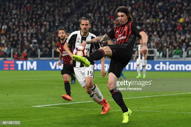 Alessio Romagnoli of AC Milan in action against Leonardo Bonucci of Juventus FC during the Serie A match between Juventus FC and AC Milan at Juventus...