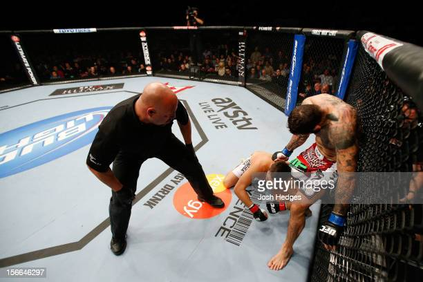 Alessio Sakara punches Patrick Cote in the back of the head as referee Dan Miragliotta looks on during their middleweight bout during UFC 154 on...