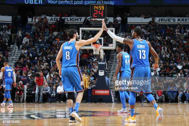 Alex Abrines and Paul George of the Oklahoma City Thunder high five during the game against the New Orleans Pelicans on November 20 2017 at the...
