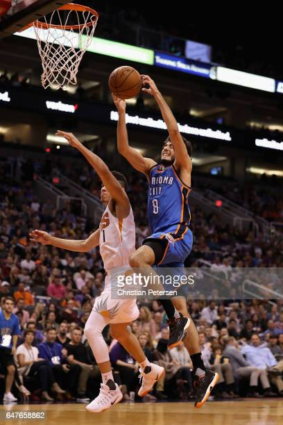 Alex Abrines of the Oklahoma City Thunder drives to the basket past Devin Booker of the Phoenix Suns during the first half of the NBA game at Talking...