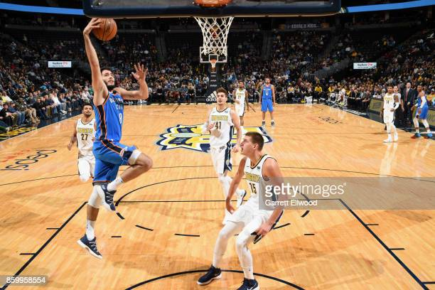 Alex Abrines of the Oklahoma City Thunder goes to the basket against the Denver Nuggets on October 10 2017 at the Pepsi Center in Denver Colorado...