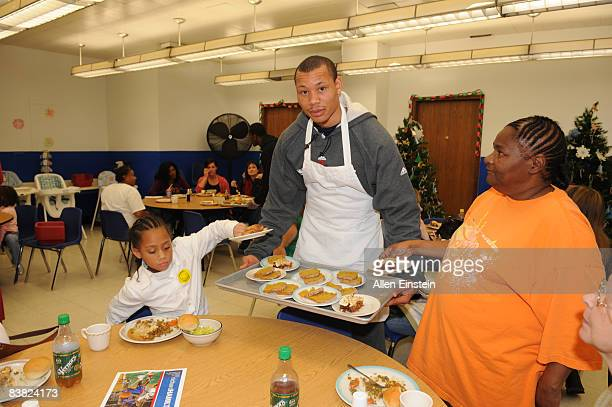Alex Acker of the Detroit Pistons serves desert during the Thanksgiving Celebration for 150 individuals and families hosted for the seventh year by...