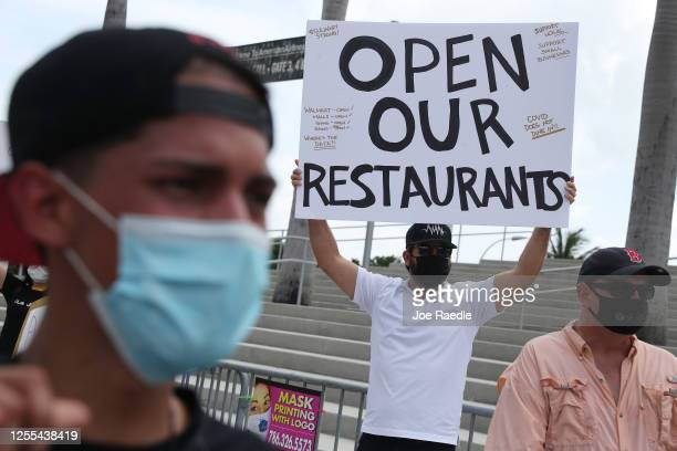 Alex Aguilar along with restaurant owners workers and supporters gather to protest new measures stating restaurants must close their indoor seating...