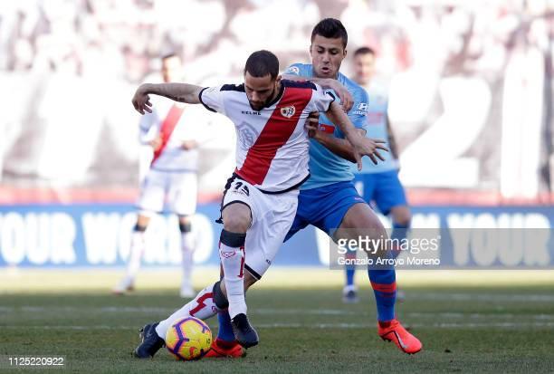 Alex Alegria of Rayo Vallecano de Madrid is challenged by Rodrigo during the La Liga match between Rayo Vallecano de Madrid and Club Atletico de...