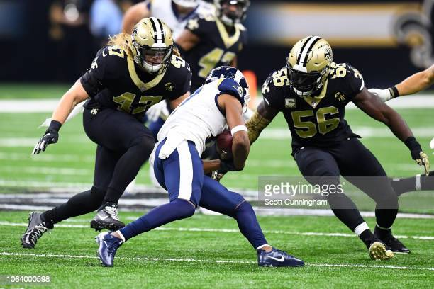 Alex Anzalone and Demario Davis of the New Orleans Saints prepare to make a tackle against the Los Angeles Rams at the Mercedes Benz Superdome on...