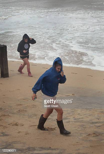 Alex Askew and Alina Power shield their faces from blowing sand as they walk along the beach during Hurricane Irene August 27, 2011 in Kill Devil...