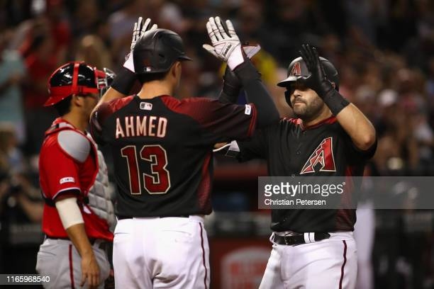 Alex Avila of the Arizona Diamondbacks high fives Nick Ahmed after hitting a two-run home run against the Washington Nationals during the fifth...