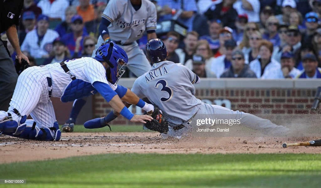 Alex Avila #13 of the Chicago Cubs tags out Orlando Arcia #3 of the Milwaukee Brewers at the plate in the 5th inning at Wrigley Field on September 9, 2017 in Chicago, Illinois.