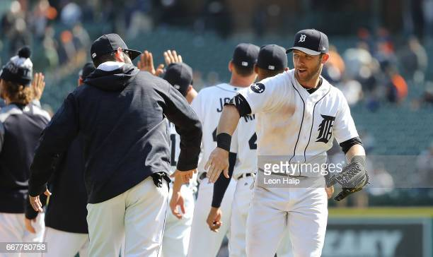 Alex Avila of the Detroit Tigers congratulates teammate Andrew Romine after the win over the Minnesota Twins on April 12 2017 at Comerica Park in...