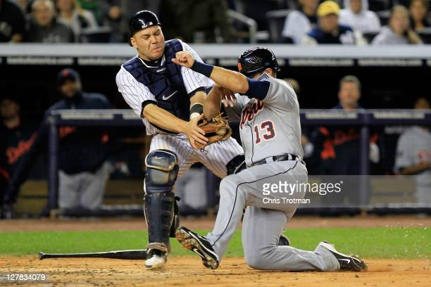 Alex Avila of the Detroit Tigers is tagged out at home plate by Russell Martin of the New York Yankees in the fourth inning of Game One of the...
