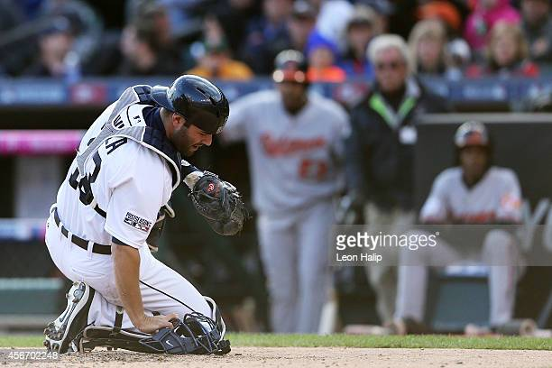 Alex Avila of the Detroit Tigers reacts after being hit with a foul tip in the sixth inning against the Baltimore Orioles during Game Three of the...