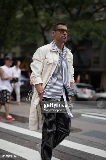 Alex Badia is seen attending Deveaux at EN Japanese Brasserie during Men's New York Fashion Week wearing a long white coat with striped pants and...