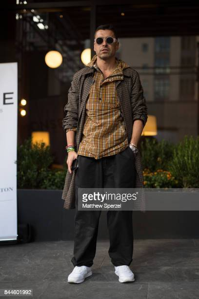 Alex Badia is seen attending Monse during New York Fashion Week wearing a long tweed coat with flannel shirt on September 8 2017 in New York City