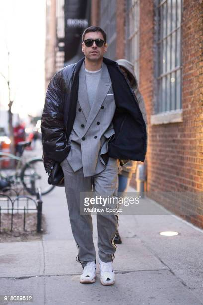 Alex Badia is seen on the street attending Boss Women during New York Fashion Week wearing a grey suit with black coat on February 13 2018 in New...