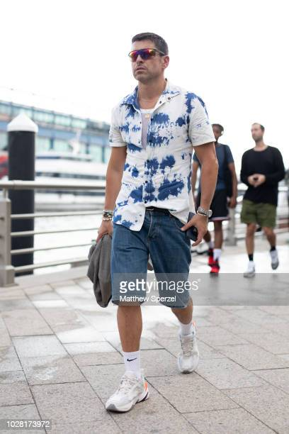 Alex Badia is seen on the street attending New York Fashion Week SS19 wearing white/navy pattern shirt with denim shorts and white sneakers on...