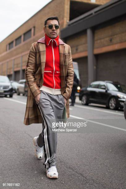Alex Badia is seen on the street attending Ralph Lauren during New York Fashion Week wearing a brown plaid coat with red sweater and grey track pants...