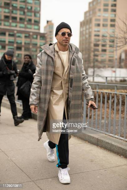 Alex Badia is seen on the street during New York Fashion Week AW19 wearing plaid coat with khaki coat and cream sweater and beanie on February 11...