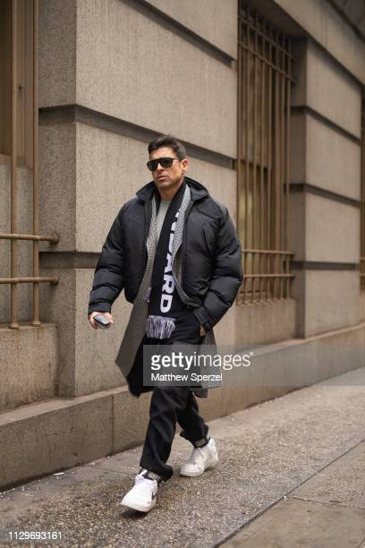 Alex Badia is seen on the street during New York Fashion Week AW19 wearing black down coat with scarf and white sneakers on February 13 2019 in New...