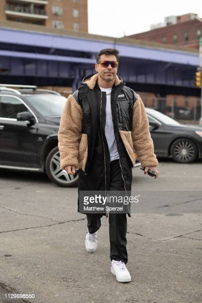 Alex Badia is seen on the street during New York Fashion Week AW19 wearing tan/black fleece coat and white sneakers on February 13 2019 in New York...