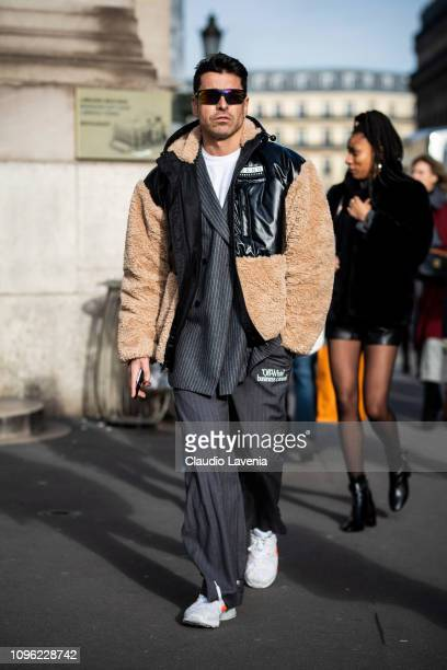 Alex Badia wearing a black jacket with fur details grey striped blazer grey OffWhite pants and white shoes is seen in the streets of Paris before the...