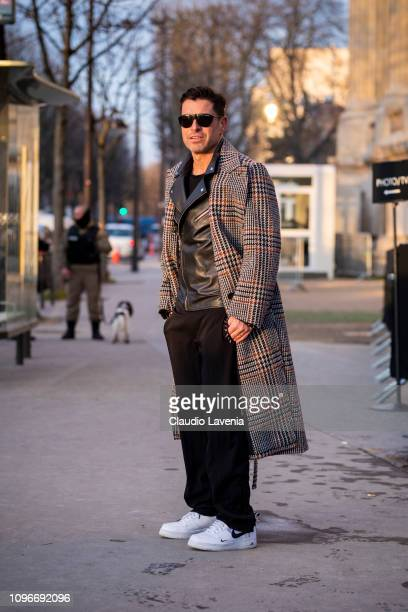 Alex Badia wearing a black leather jacket black pants white shoes and checked coat is seen in the streets of Paris before the Sacai show on January...