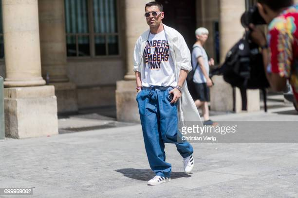 Alex Badia wearing a creme coat navy pants white tshirt with print Adidas superstar sneakers outside Louis Vuitton during Paris Fashion Week Menswear...