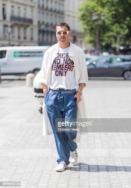 Alex Badia wearing a creme coat navy pants white tshirt with print Adidas superstar sneakers outside Louis Vuitton during Paris Fashion Week Menswear...