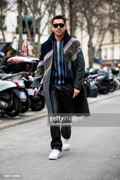Alex Badia wearing a Fendi coat black leather pants striped sweatshirt and white sneakers is seen in the streets of Paris before the Acne Studio show...
