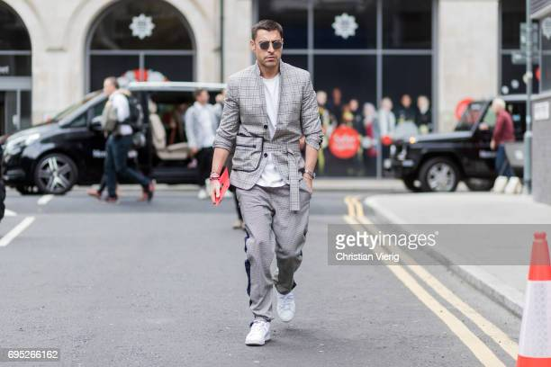 Alex Badia wearing a grey suit during the London Fashion Week Men's June 2017 collections on June 12 2017 in London England