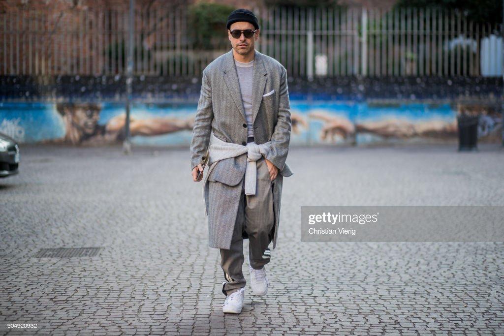 Alex Badia wearing a grey wool coat, beanie, grey track suit pants is seen outside Daks during Milan Men's Fashion Week Fall/Winter 2018/19 on January 14, 2018 in Milan, Italy.