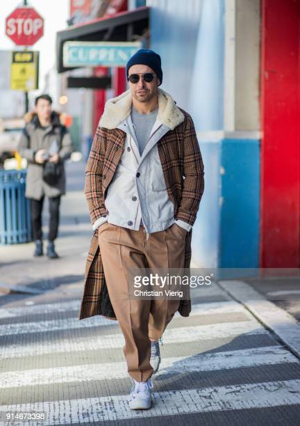 Alex Badia wearing brown checked coat, brown pants, wool hat is seen during Mens' New York Fashion Week on February 5, 2018 in New York City.