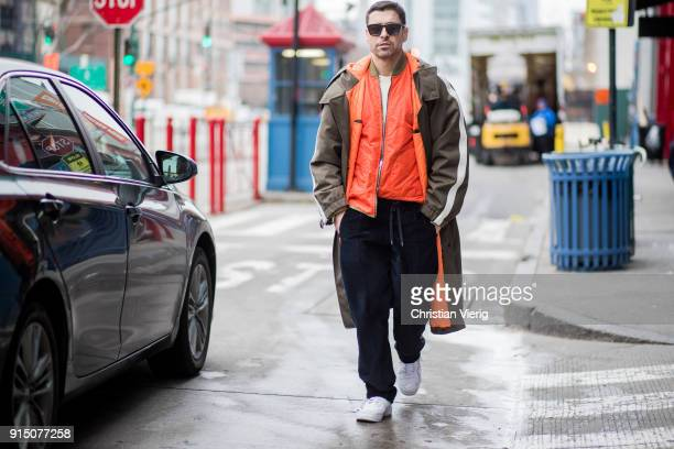Alex Badia wearing coat orange jacket navy pants white sneakers seen during Mens' New York Fashion Week on February 6 2018 in New York City
