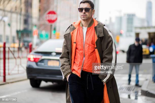 Alex Badia wearing coat orange jacket navy pants white sneakers seen during Mens' New York Fashion Week on February 6 2018 in New York City